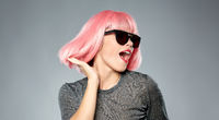 happy woman in pink wig and sunglasses dancing
