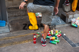Singapur, Republik Singapur, Mann mit Gummistiefel zertritt leere Getraenkedosen