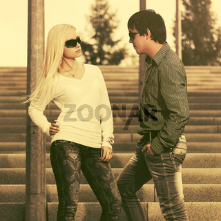 Happy young fashion couple flirting on steps