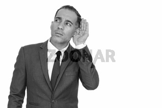 Mature handsome Persian businessman listening in black and white