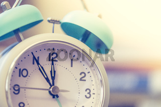 Alarm clock on the desk, books in the blurry background, deadlines and todos