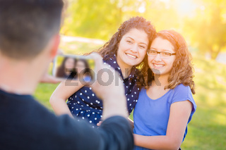Hispanic Father Taking Picture of Mother and Daughter with Cell Phone