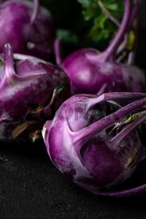 Purple kohlrabi. Shooting on a black background in a low key.