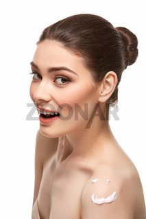 girl applying moisturizing cream isolated on white
