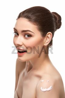 girl applying moisturizing cream isolated on white