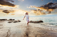 Young happy woman running on the beach