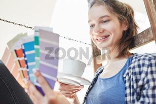 Frau schaut auf Farbfächer und sucht Wandfarbe aus