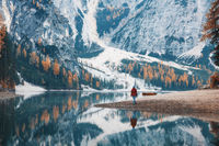Woman on the coast of Braies lake in the morning in autumn