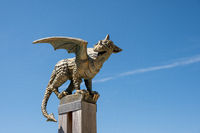 Bronze dragon statue on pole isolated on blue sky