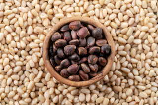 Pine nuts in a round wooden bowl on a background of peeled pine nuts.