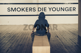 Teenager smoking and message on wall - Smokers die younger. No smoking concept
