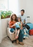 Happy family sitting at armchair studying globe.
