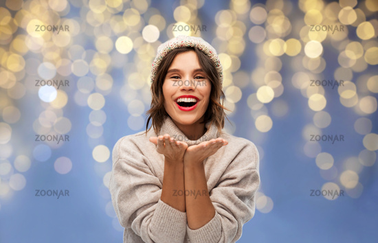woman in winter hat sending air kiss on christmas