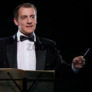 Orchestra conductor in black tuxedo in dark studio