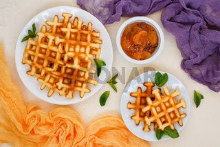 Top view of Belgian waffles on beige table.