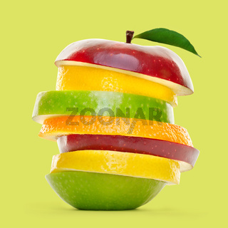 Mixed fruit slices piled up and isolated on green background
