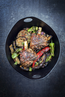 Traditional barbecue leg of lamb with eggplant and chili as top view in a modern style Japanese cast-iron roasting dish with copy space