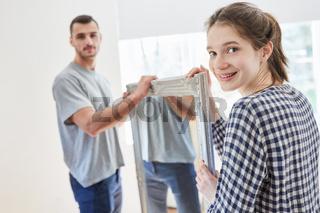 Paar trägt gemeinsam einen Spiegel beim Umzug