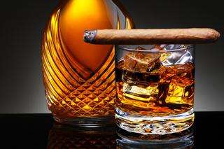 Closeup of an elegant decanter and a glass of scotch on the rocks with a lit cigar laying across the top of the glass. Horizontal on a light to dark gray background.