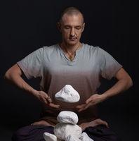 Man meditating on the floor in yoga pose in studio