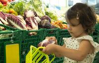 Child shopping radicchio in supermarket.