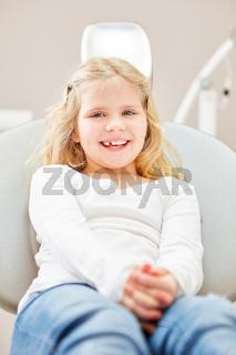 Fröhliches Mädchen sitzt angstfrei beim Zahnarzt