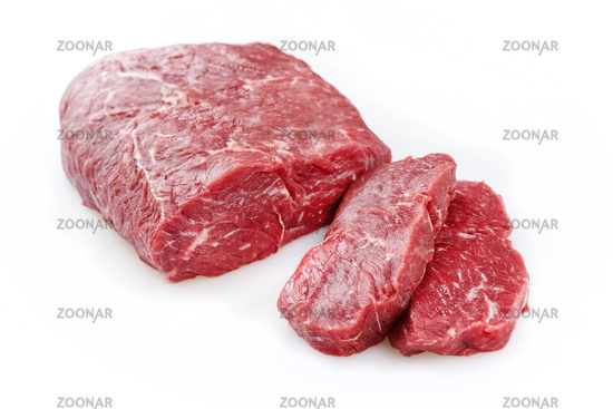 Raw roast beef as piece and slices offered as closeup on white background – isolated