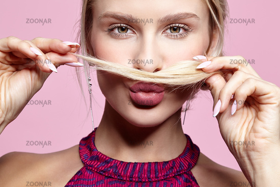 Young woman holds hair under nose like a mustache