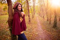 Beautiful girl in stylish fall fashion clothes in park scenery, in nice warm autumn sunlight. Gorgeous romantic young woman outdoors. American plan shot in natural light, retouched, vibrant colors