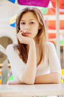 Young beautiful woman with long hair sitting at table