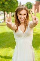 a beautiful young Woman in a white dress and shows fingers laughs sign of victory