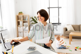 mother working at laptop and baby playing at home