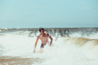 Young man enjoying the high waves in the sea during a summer vacations