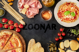 Italian food. Pizza, pasta, cheese, ham, wine, olives, pesto, olive oil, capers, shot from the top forming a frame with a place for text, a flat lay design template on a dark background