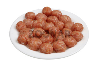 Small raw pork meatballs for meat soup are on the plate isolated macro