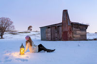 Woman with lantern sitting in a snow covered field