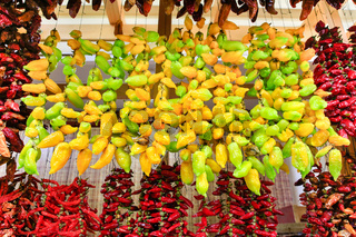 Many yellow and red peppers hanging on market