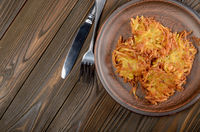 Fresh homemade tasty potato pancakes in clay dish on wooden table