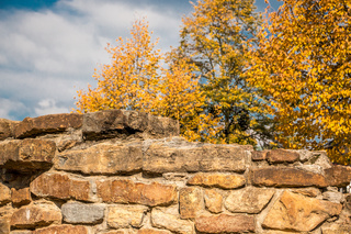 Strong stone wall and yellow autumn leaves
