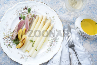Traditional sliced pork fillet steak with white asparagus in butter sauce and roast potatoes as top view on a classical plate