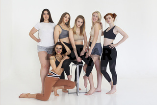 Happy different race women wearing sports top and leggings