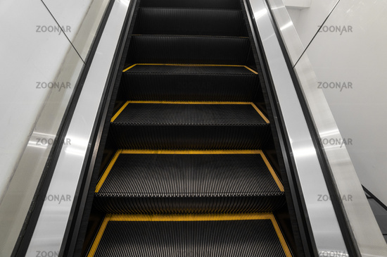 Modern escalator electronic system moving. Escalator is moving up.The ground is a straight line. Black with yellow band.