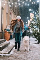 Woman walking down with white dog by alley.