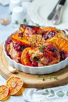 Chicken thighs baked with orange, garlic and cherry.