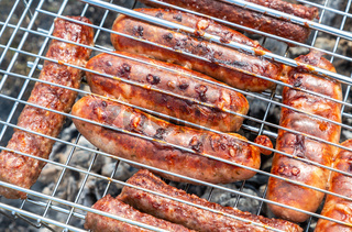 Appetizing sausages from meat on a metal grid