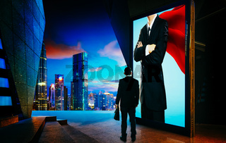 Young businessman looking the hero businessman on the advertising billboard screen . Successful businessman concept .