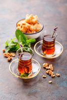 Traditional Turkish arabic dessert and a glass of tea with mint