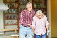 Senior stützt seine behinderte Ehefrau mit Krücken