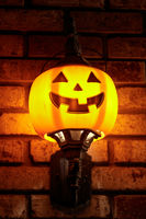 Halloween pumpkin light fixture decorating a brick wall.