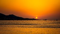 Solar disc in sunrise with silhouette of mountains, panorama, Mallorca, Spain